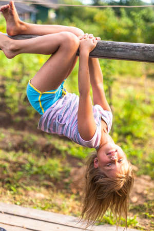 Little girl having fun in park hanging upside down on green rural countryside. Stock Photo