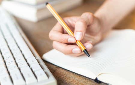 De escritura a mano, mano femenina escribe con una pluma en un cuaderno diario.