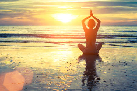 yoga meditation: Silhouette of yoga woman meditating on the ocean beach. Fitness. Healthy lifestyle. Stock Photo