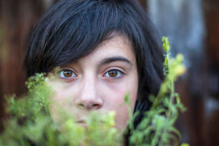 eyes hidden: Closeup of black-haired teen girl with expressive eyes, hidden in the greenery of the garden. Emo.