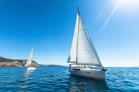 Sailing regatta. Luxury yachts. Sailing in the wind through the waves at the Aegean Sea in Greece.