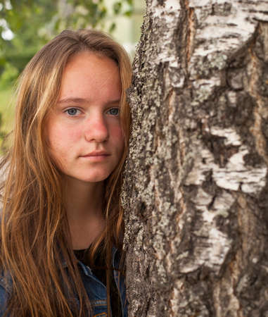 Young cute teen girl with long hair portrait near the tree. photo