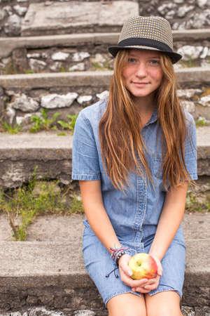 cute teen girl: Симпатичные девушки подростка в парке с яблоком в руке.