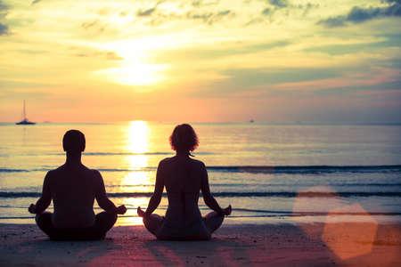若い男性と女性の驚くべき日没時に海ビーチにロータスの位置でヨガの練習のシルエット。