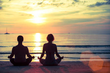 Silhouette of young man and woman practicing yoga in the lotus position on the ocean beach during amazing sunset. photo