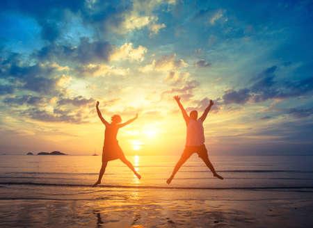 Hochzeitsreise. Junges Paar Springen auf dem Meer Strand bei traumhaften Sonnenuntergang. Urlaub und Natur.