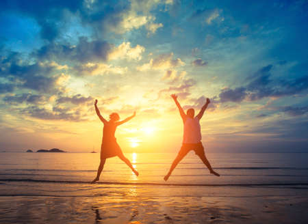 fun in the sun: Honeymoon. Young couple jumping on the sea beach during amazing sunset. Vacation and Nature. Stock Photo
