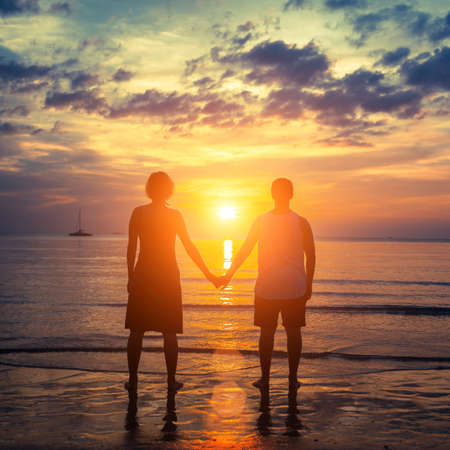 Silhouette of a young couple on their honeymoon standing on the ocean beach at amazing sunset. photo