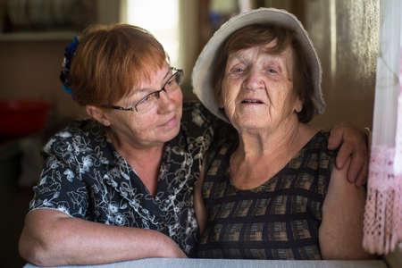 personas abrazadas: Retrato de la mujer mayor y su hija en la casa. Foto de archivo