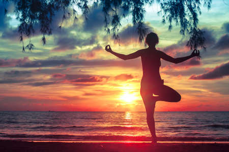 Silhouette young woman practicing yoga on the sea beach at blood-surrealistic sunset. Stockfoto