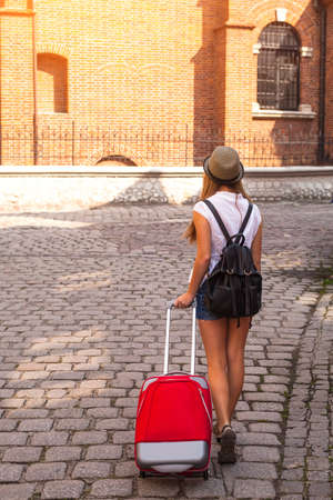 bstract: Young cute girl travels through the cities of old Europe. An аbstract girl - rear view, pavement, red suitcase.