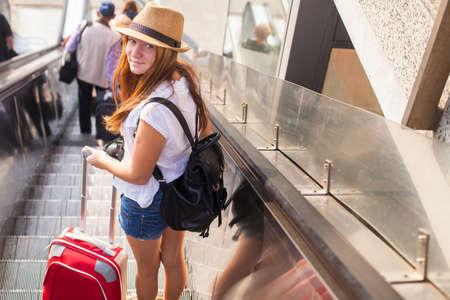 gente aeropuerto: Linda chica joven con la maleta roja que se coloca en la escalera mecánica. Concepto del recorrido.