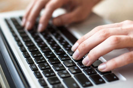 Close-up of female hands typing text on the keyboard of laptop or computer.