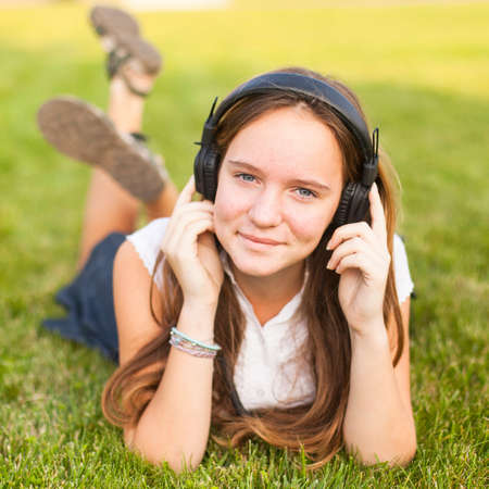 Young girl in headphones enjoys the music lying on the green grass. photo