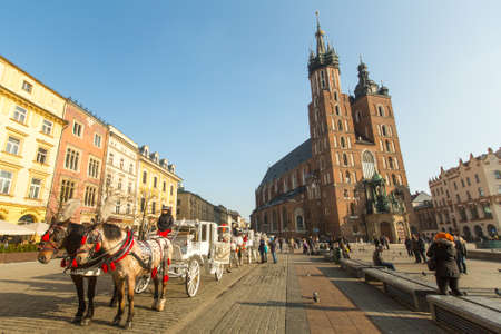KRAKOW, POLAND - FEB 7, 2015: St. Marys Church in historical center of Krakow on Main Square - dates to the 13th century, and at roughly 40,000 m it is the largest medieval town square in Europe.