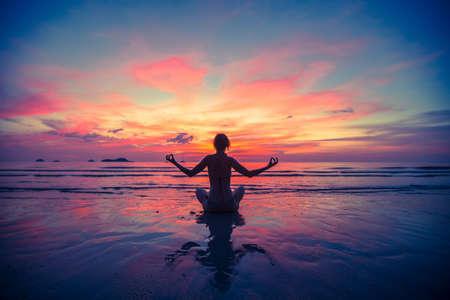 mujer meditando: Mujer que hace la meditación, cerca de la playa del océano. Silueta de la yoga.