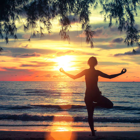 Silhouette of a young woman practicing yoga in the rays of the surrealist sunset at seaside. photo