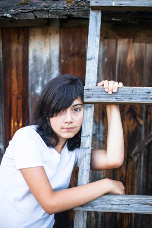 emo: Black-haired teen girl with expressive eyes, a portrait in the countryside. Emo.