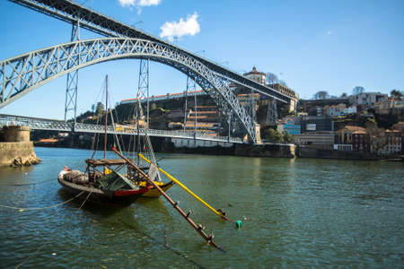 recognised: PORTO, PORTUGAL - FEB 17, 2015: Ribeira, traditional boats at Douro river in Old Town, Luiz iron bridge in background. In 1996, UNESCO recognised Old Town of Porto as a World Heritage Site.