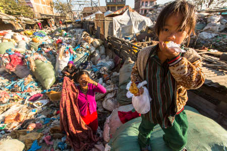 KATHMANDU, NEPAL - CIRCA DEC, 2013: Unidentified child and his parents during lunch in break between working on dump. Only 35% of population Nepal have access to adequate sanitation. 에디토리얼
