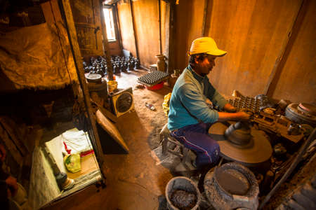 rotates: BHAKTAPUR, NEPAL - CIRCA DEC, 2013: Unidentified Nepalese man working in the his pottery workshop. More 100 cultural groups have created an image Bhaktapur as Capital of Nepal Arts.
