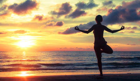 subtropics: Silhouette of a woman practicing yoga during a beautiful sunset on the beach in subtropics. Stock Photo