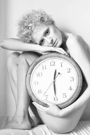 black and white photography: Beautiful young girl with curly hair sitting on the bed with a big clock in his hands. Black and white photography.