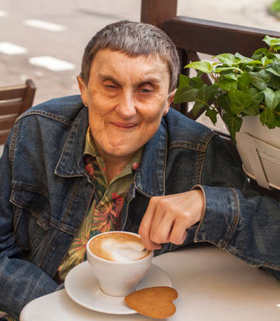 cerebral palsy: Disabled man with cerebral palsy sitting at outdoor cafe with a cup of coffee.