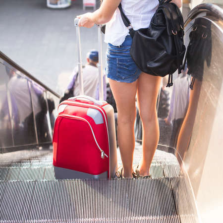 Young girl with the red suitcase standing on the escalator. Travel concept.