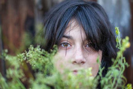 caras tristes: Retrato del primer de la muchacha adolescente de pelo negro, oculto en la vegetaci�n del jard�n.