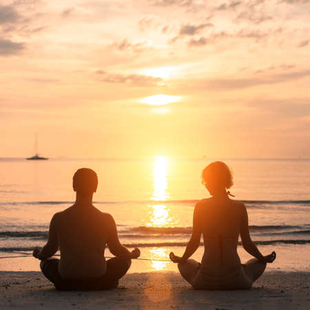2 people: Young couple practicing yoga on Sea beach during sunset.
