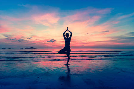 Silhouette of woman standing at yoga pose on the beach during an amazing sunset.