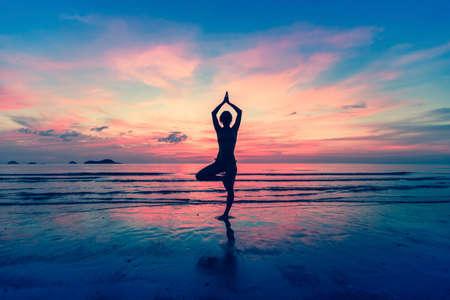 요가에 서있는 여자의 실루엣이 놀라운 일몰 동안 해변에서 포즈.