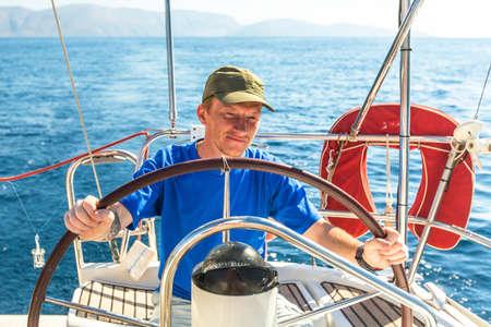 skipper: Young man skipper at the helm controls sailing yacht.