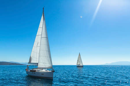 Sailing. Yachting. Tourism. Luxury Lifestyle. Ship yachts with white sails in the open sea.