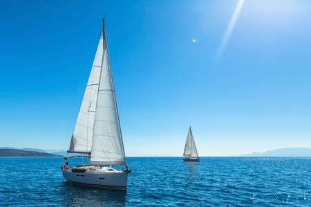 Segeln. Yachting. Tourismus. Luxury Lifestyle. Lieferungsyachten mit weißen Segeln auf dem offenen Meer.