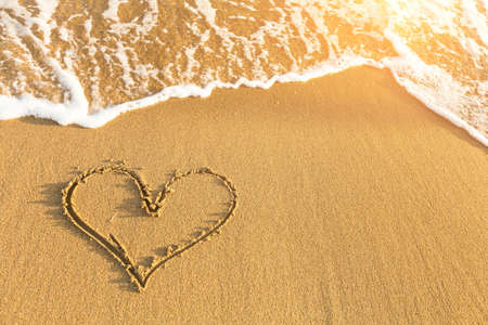 evoking: Heart drawn in sea beach sand, soft wave in a Sunny summer day.