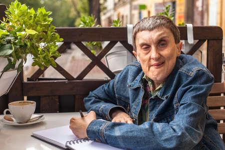discapacidad: Hombre lisiado con par�lisis, sonriente, sentado en un caf� al aire libre. Foto de archivo