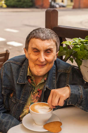 cerebral palsy: Portrait of elderly disabled man with cerebral palsy, at an outdoor cafe.
