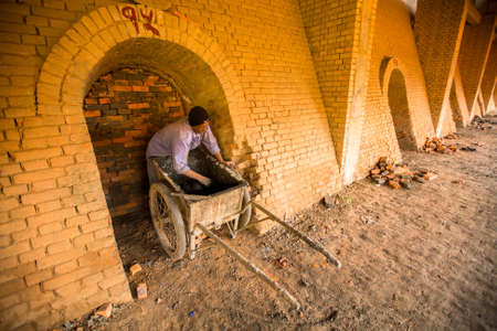 deprived: BHAKTAPUR, NEPAL - CIRCA DEC, 2013: Unidentified local people work at the Brick Factory. Nepal as a whole has been categorized as the 4th most vulnerable country in the world due to climate change.