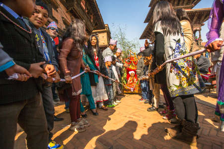 7 months: BHAKTAPUR, NEPAL - CIRCA DEC, 2013: Unidentified children during Birthday celebration head of family - 77 years 7 months 7 days 7 hours old, like rebirth according to Newar.