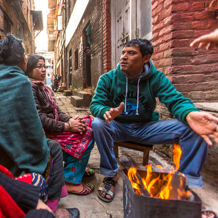 rigid: BHAKTAPUR, NEPAL - CIRCA DEC, 2013: Unidentified local people sit in the street. The caste system is still intact today but the rules are not as rigid as they were in the past. Editorial