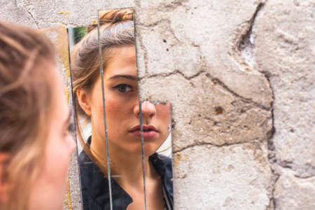 espejo: Muchacha adolescente que mira su reflejo en los fragmentos del espejo en la pared en la calle.