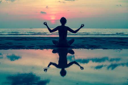 mujer meditando: Silueta de la yoga. Chica haciendo meditaci�n en la playa del oc�ano. Con reflejo en el agua. Foto de archivo