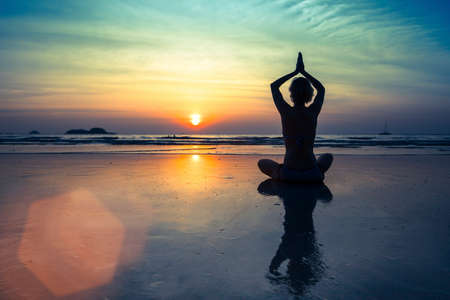 Female silhouette in Yoga meditation pose at amazing sunset.