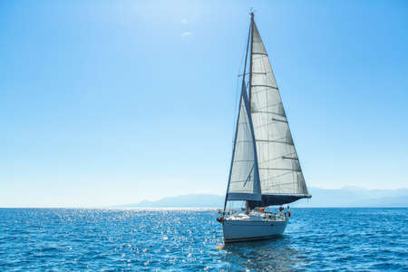 recreation yachts: Sailing ship yachts with white sails in the open Sea. Luxury boats. Stock Photo