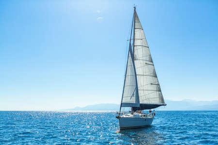 horizonte: Vela yates barco con velas blancas en el mar abierto. Barcos de lujo.