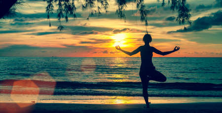 surrealistic: Silhouette young woman practicing yoga on beach at surrealistic sunset. Stock Photo