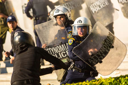 riots: ATHENS, GREECE - APR 16, 2015: Riot police with their shield, take cover during a rally in front of the Athens University, which is under occupation by protesters leftist and anarchist groups.