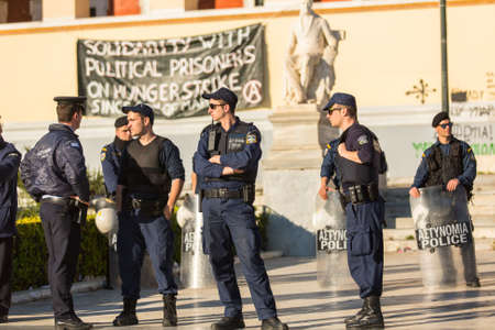 anarchist: ATHENS, GREECE - APR 16, 2015: Riot police with their shield, take cover during a rally in front of the Athens University, which is under occupation by protesters leftist and anarchist groups.